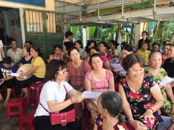 Nhân viên Bưu điện tuyên truyền chính sách hỗ trợ tiền đóng BHXH tự nguyện đến người dân khu vực Cồn Hến (Tp Huế)